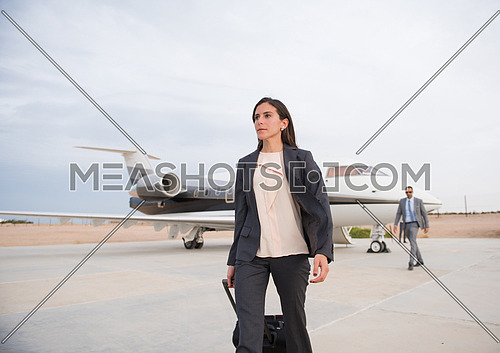 young middle eastern successful woman walking in front of private airplane
