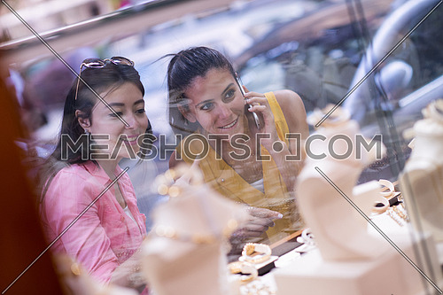 two middle eastern young women enjoy as they watch jewelry in the window of a luxury jewelry store
