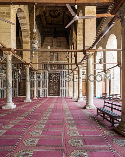 Corridor at public historic mosque of Sultan Al Moaayad, ending with colorful marble wall and wooden door decorated with arabesque ornaments, Old Cairo, Egypt