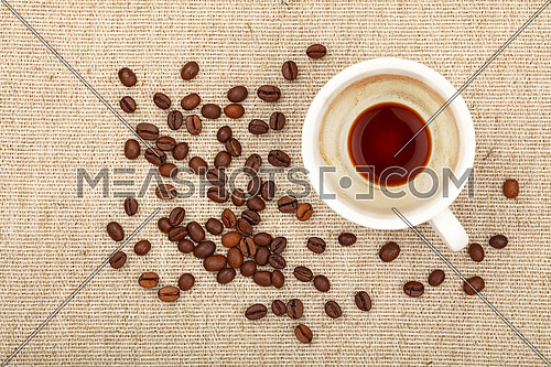 One empty finished white cup of espresso or americano and roasted coffee beans on background of linen canvas