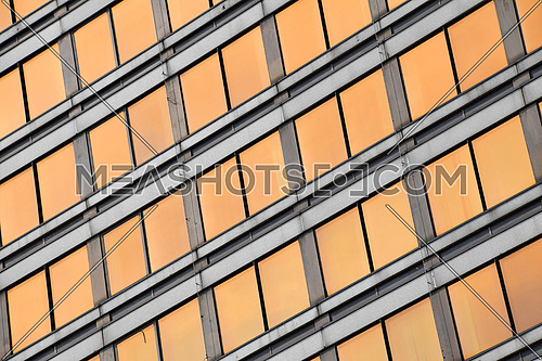 Orange colored glass windows of modern business office building at sunset in evening, diagonal perspective, low angle view, close up