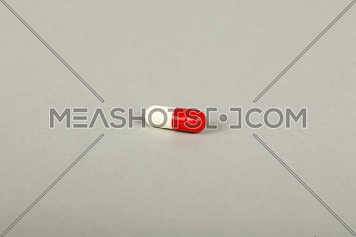 Close up one red and white gel cap pill of medicine over grey background with copy space, high angle view