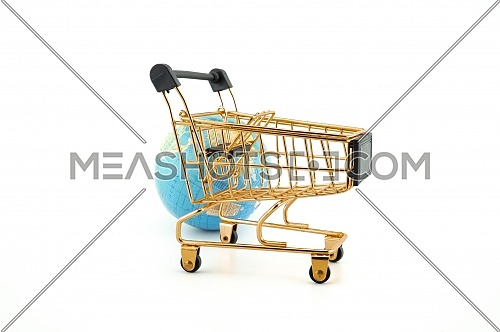 Golden shopping cart in front of a world globe isolated on white background