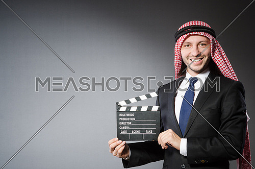 Arab man with movie clapper isolated on white