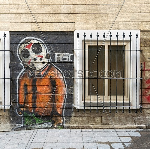 Istanbul, Turkey - April 18, 2017: Beige bricks external wall with graffiti drawing and single windows near Istiklal Street
