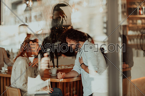 a woman in glasses and men with afro hair sit in a cafe and talk about business projects