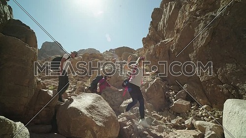 Track In shot for group of tourists go down on big rocks with bedouin guide to explore Sinai Mountain for wadi Freij at day.