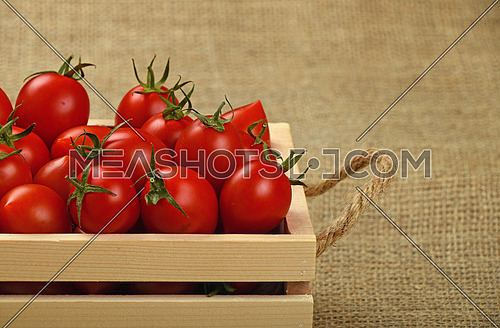 Red ripe fresh cherry tomatoes in small wooden box with twine jute handles on burlap canvas background