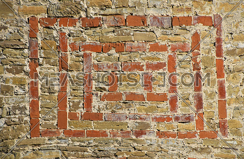Antique stone wall texture with red bricks hacking ornament pattern, close up