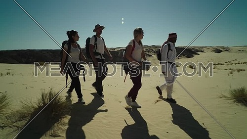 Follow shot for group of tourists and bedouin guide spreading Egyptian flag while exploring Sinai Trail from Ain Hodouda at day.