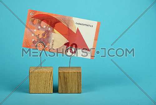 European economy crisis, decline of Euro currency, ten Euro banknote with red arrow down at wooden metal holders over blue background