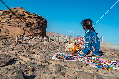 mid Shot for a little girl sits beside stone house Called Nawamis area from Sinai Trail at day.