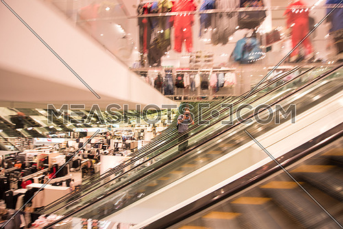 photographer working on the escalator of a large modern shopping center