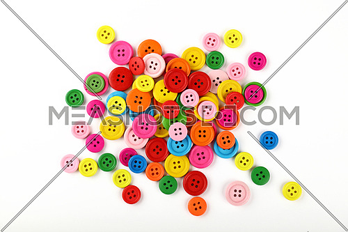 Mix of assorted colorful multicolor round painted wooden handmade sewing buttons over white background, close up, elevated top view