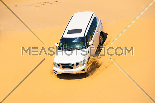 An SUV dune bashing in the desert