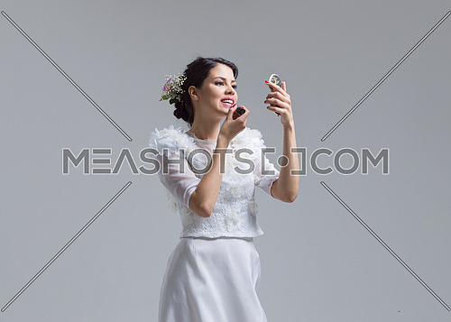 bride paints lips with lipstick on their wedding day in dress isolated on a white background