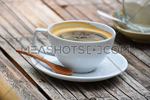 One full white cup of Americano long coffee on porcelain saucer with wooden spoon on old vintage bamboo table