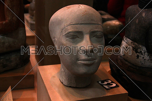 a photo from inside the Egyptian museum showing a display for ancient statue head belonging to the pharaohs civilization