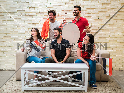 group of young people sitting on a sofa cheering for a football match in front of white table holding egyptian flags and drum