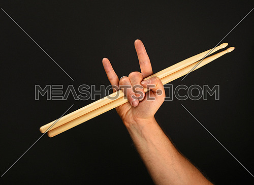 Man hand holding two wooden drumsticks with devil horns rock metal gesture sign over black background, front view