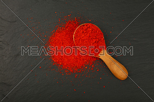Close up one wooden scoop spoon full of red chili pepper or paprika powder on background of black slate board, elevated top view, directly above