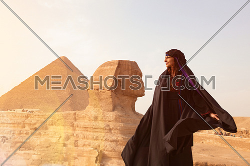 egyptian woman in traditional beduin clothes in front of ancient great giza pyramids  and sphinx profile