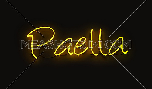 Close up PAELLA yellow neon light sign glowing in the dark over black wall background