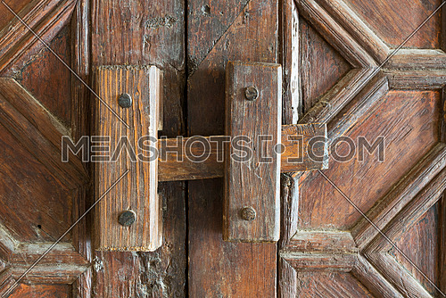 Closeup of a wooden aged latch over an ornate wooden old door, Qalawun Complex, Cairo, Egypt