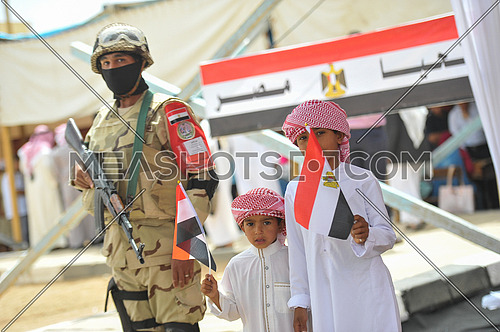 Sinai Bedouin children carrying the flag of Egypt next to an Egyptian army soldier waiting for their father's exit after the vote in the 2018 presidential elections in the city of peace Sharm el-Sheikh in South Sinai on the first day of the elections March 26, 2018, which lasts for 3 days