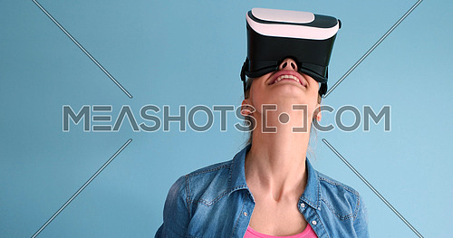 Happy girl getting experience using VR headset glasses of virtual reality, isolated on blue background
