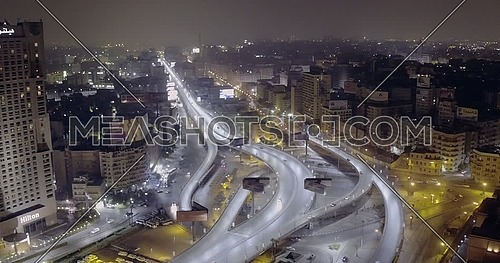 360 Drone shot for 6 of October Bridge over Abd Elmonan Reyad Bus Station showing Hilton Hotel At Tahrir Area in cairo at night