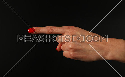 Woman hand with red nails showing direction or pointing with index finger gesture isolated on black background, side view