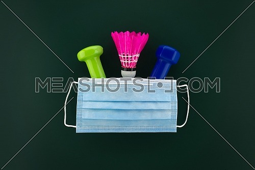 Dumbbells, shuttlecock covered with a protective surgical face mask. Activity during the quarantine period concept with free copy space