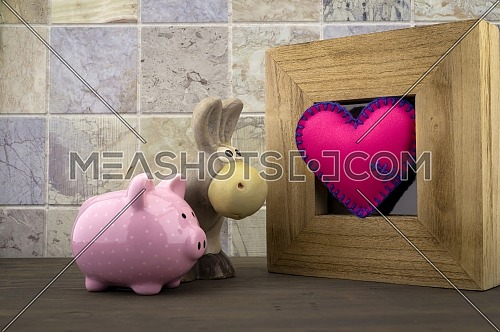 Cute little piggy bank and toy donkey with a handcrafted pink heart in a wooden frame against a tiled background