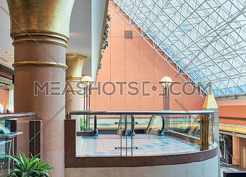 Modern shopping mall interior with glass balustrade transparent glass roof revealing blue sky