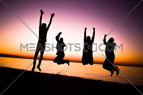 four friends jumping at the beach by sunset magic hour