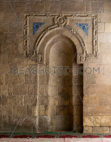 A stone wall with a sculpted Mihrab and few decorations in a historic mosque in Old Cairo, Egypt