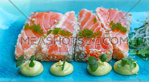 Close up portion of fresh raw salmon fish sashimi with sesame seeds, salad and sauce on blue plate, high angle view