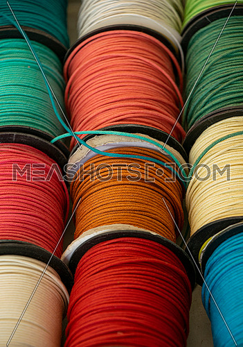Close up many colorful craft lacing spools on retail display, high angle view