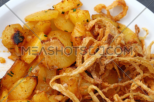 Close up portion of roasted potato and fried onion rings on white plate over grey table, elevated top view, directly above