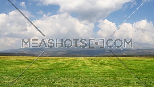 Animated cinemagraph of scenic cloudscape, blue cloudy sky over tranquil green field landscape and mountain ridge at horizon