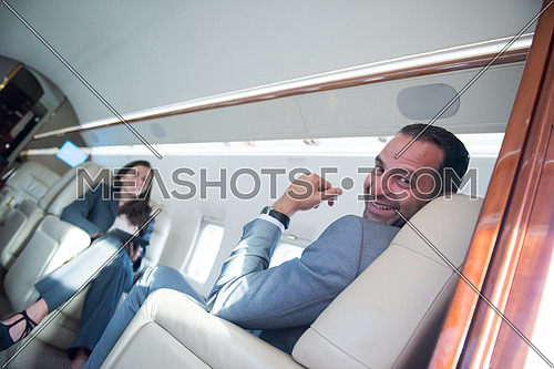 Young middle eastern successful businessman and businesswoman enjoy sitting in private jet