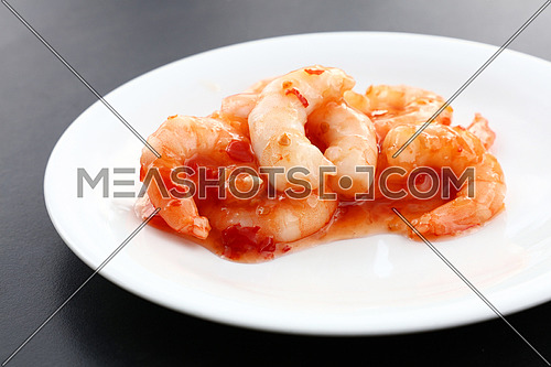 Close up portion of shrimp salad with sweet chili sauce on white plate over black table, elevated top view, directly above