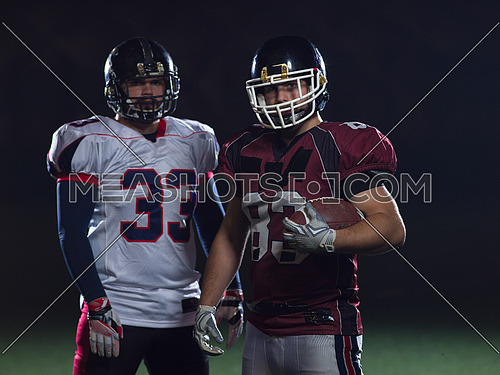portrait of confident American football players holding ball while standing on field at night