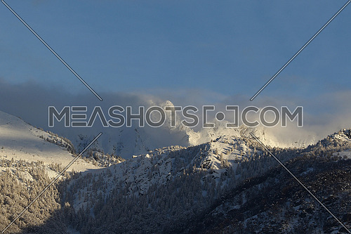 Mountain peaks and valley covered in snow with dissipating winter storm clouds and blue skies