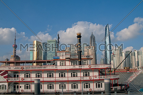 shanghai pudong view from puxi new bund with steam boat on huangpu river on foreground
