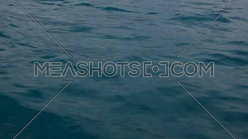 Close up background of vivid teal blue sea water waves running aboard, alongside boat during sailing, personal perspective of action camera