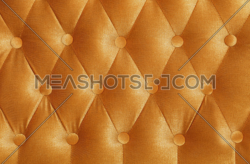 Golden orange color capitone textile background with buttons, retro Chesterfield style soft tufted fabric furniture upholstery diamond pattern decoration, close up