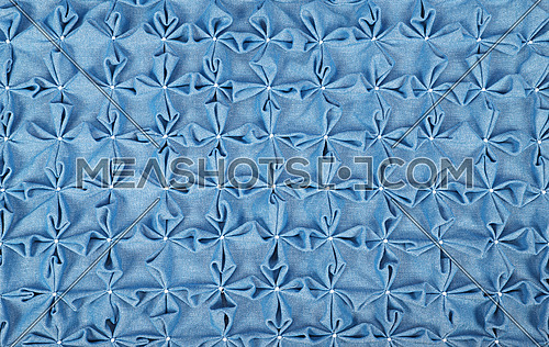 Close up background texture of blue textile puffs for Canadian smocking upholstery decoration with beads