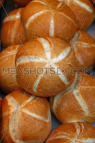 Close up several fresh wheat bread buns on retail display of bakery store, high angle view